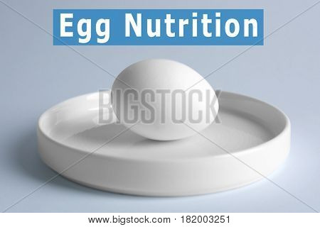 Plate with raw egg on light background. Text EGG NUTRITION