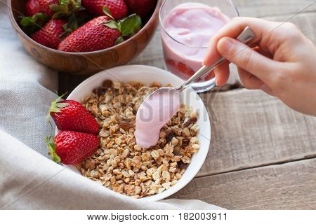 Healthy breakfast. Muesli and yogurt with strawberries. A woman's hand puts a spoonful of yogurt in the muesli.