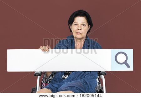Senior adult woman on wheelchair holding searching banner