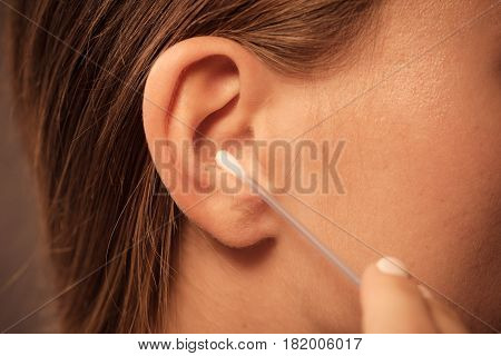 Woman Cleaning Ear With Cotton Swabs Closeup