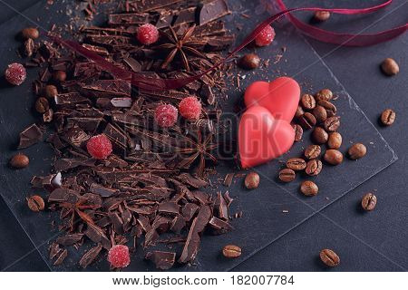 Dark chopping chocolate coffee beans red berries red chocolate with heart shape anise spice on slate board over black textural background. Chocolate dessert confectionery and sweets concept