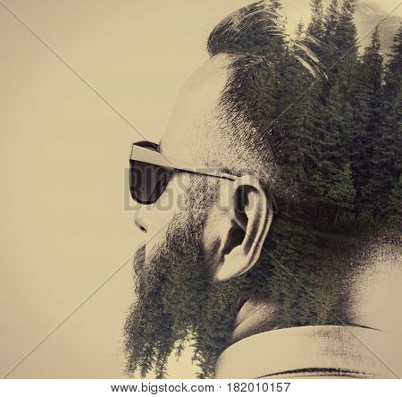 Portrait of a bearded man in sunglasses with a stylish haircut. Black and white. Image created using multiple exposures. Forest landscape is depicted on dark parts of image.