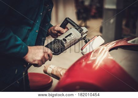 Mechanic polishning car body details in restoration workshop