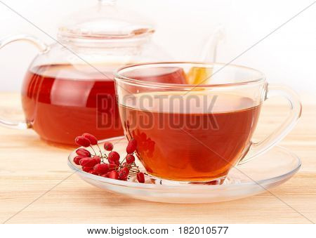 Healthy tea with barberries in glass cup on on a white background.