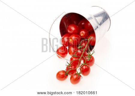 Bucket with ripe  fresh cherry tomatoes on a white background. Harvesting.