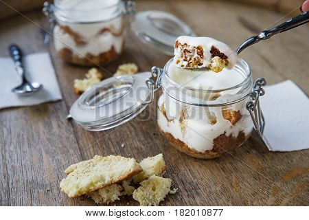 Three milk cake tres leches cake with coconut. Traditional dessert of Latin America. Serving in a jar on a wooden background.