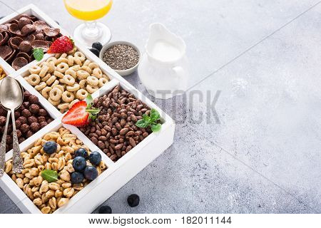 Milk jug and variety of cold quick breakfast cereals with berries in white wooden box, healthy eating concept with copy space.