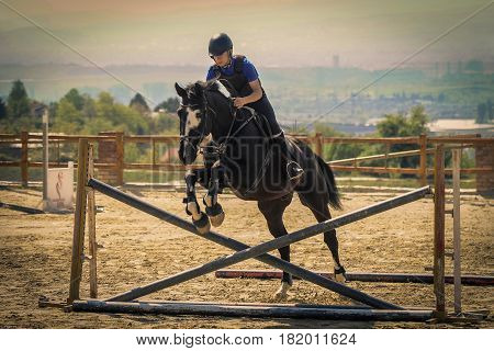 Equestrian sports Black horse approaching.The jump shooting from the rear. Jockey riding a fast thoroughbred horse
