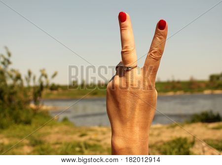 Woman's hand with two fingers up in the peace or victory symbol. Also the sign for the letter V in sign language. Against the backdrop of summer water