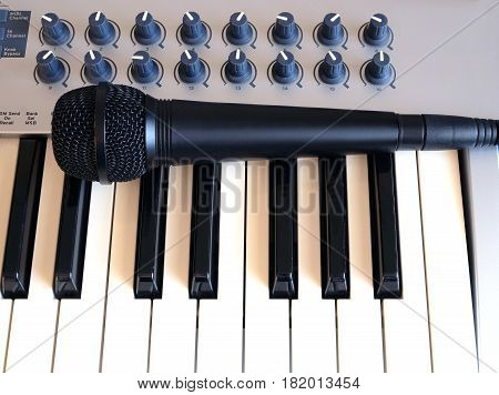 Black microphone on electronic synthesizer keyboard with many control knobs top view closeup