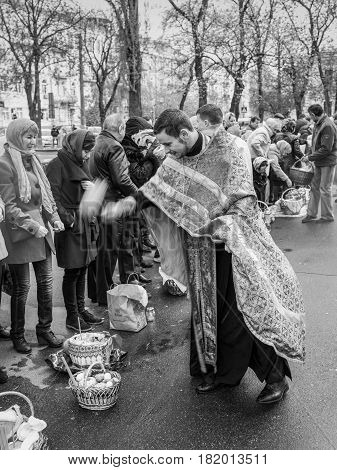 Kyiv Ukraine - April 16 2017: Priest blessing the happy people during Holy Easter Sunday ceremony outside St Volodymyr's Cathedral in Kyiv Ukraine. Black and white photography.