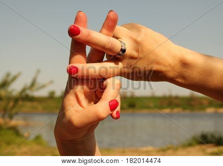 Gesture lattice. Woman hands showing hash symbol against the backdrop of summer water