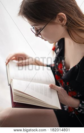 Beautiful girl sitting at home and reading interesting book. Look in the book