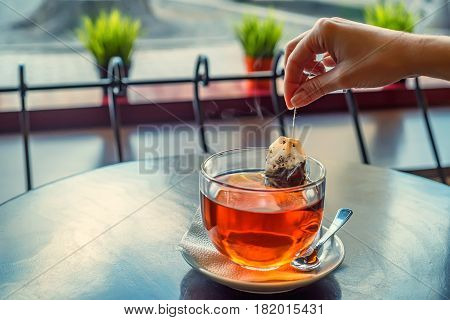 Woman's hand making cup of tea with tea bags