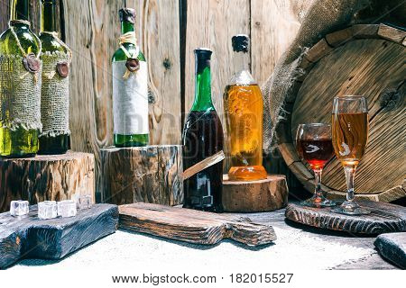 Wine bottles and wineglasses on raw wood bar counter or showcase. Natural stumps, burlap, oak barrel and rustic serving boards