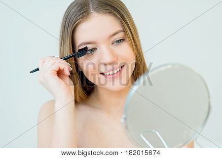Woman using curler tool for eyelashes in the bathroom