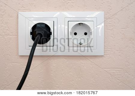 Close-up of two sockets, one with plug and one is free