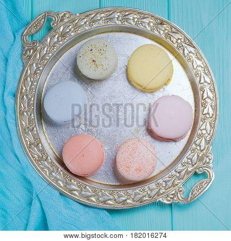Sweet colorful cookies macaroons on silver vintage salver