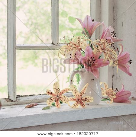 lilies bouquet on a window sill in a sunny day