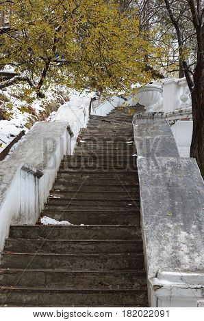 Old concrete stairs with white railing and decorative vase