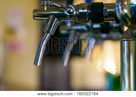 Close-up of modern beer taps in pub