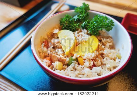 Asian cuisine - Tori tyahan. Fried rice with chicken meat vegetables and radishes in bowl.