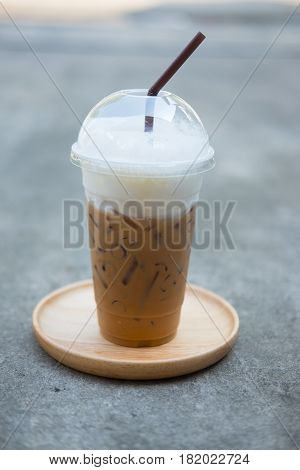 Iced coffee with straw on saucer in plastic cup at coffee shop