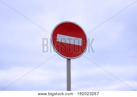 Road sign prohibiting the entry of cars against the blue sky and clouds
