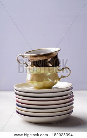 Empty colorful porcelain tableware, cups and plates on lilac background. Vertical