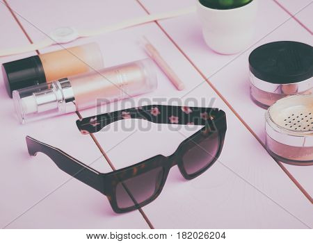 Sunglasses, cosmetics makeup and essentials on wooden background.