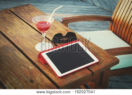 cocktail, touch pad and glasses in summer cafe, relax and modern technology