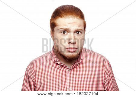 Shocked surprised bearded readhead businessman with red shirt and freckles looking at camera. studio shot isolated on white.