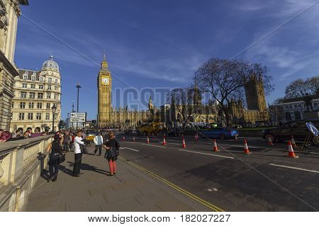 London England - 9th of April 2017: Tourists near Big Ben and Parliament in the City of Westminster in London on a warm and sunny day.