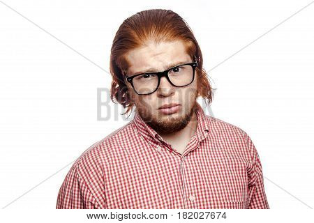 Sad unhappy bearded readhead businessman with red shirt and freckles and glasses looking at camera. studio shot isolated on white.