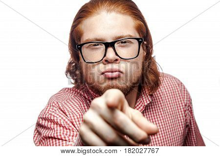 Funny bearded readhead businessman with red shirt and freckles looking at camera and pointing finger to you. studio shot isolated on white.