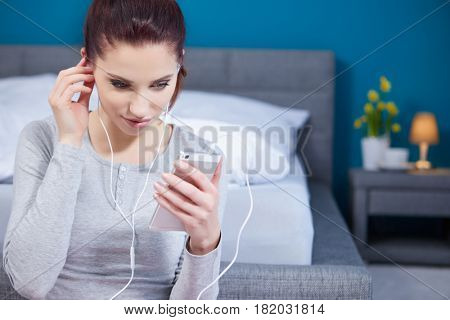 Young cheerful woman shuffling songs on mobile phone. Relaxed girl listening music with headphone at home. Happy woman in casual enjoying music in bedroom while texing a message phone.