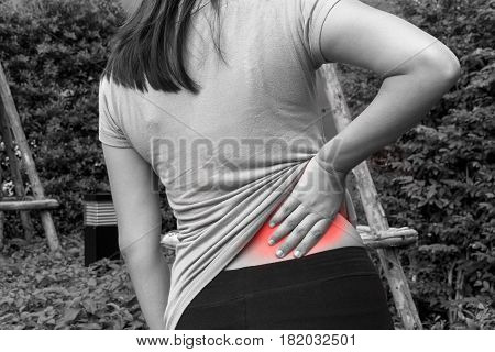 Female athlete lower back painful injury. Sporty woman backache and injury - black and white concept