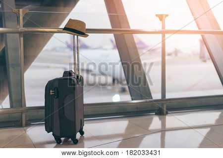 Suitcase and hat in international airport departure lounge airplane in background traveler concept traveler baggage and hat in airport terminal waiting area focus on luggage