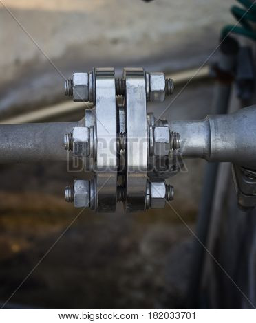 Close up steel pipe flange connected by tighten bolt ands nuts