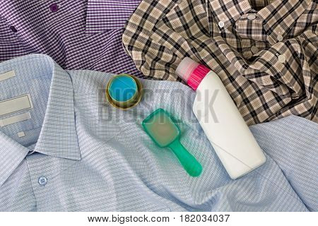 Spoon cap full of liquid laundry washing detergent, blue softening liquid, bottle of pre wash stain remover on used clothes