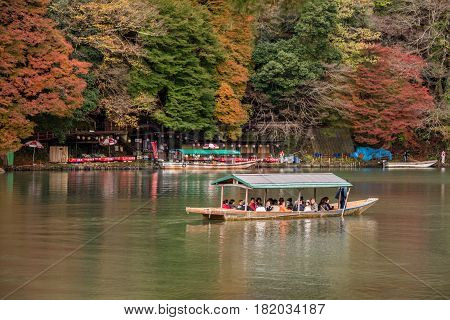 Kyoto Japan - November 262015 : Unidentified people sail boates in the Oi river for tourist who travel to Arashiyama mountain area in Kyoto Japan.