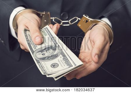 Businessman in a suit with handcuffs arrested offering bribery money for his release. Selective focus