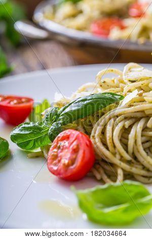 Spaghetti. Italian pasta spaghetti with basil pesto cherry tomatoes and olive oil.