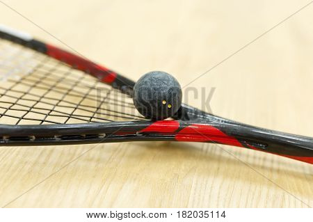 squash racket and ball on the floor. Closeup of racquetball equipment on the court. Photo with selective focus. Sport, games on the court, healthy lifestyle concept