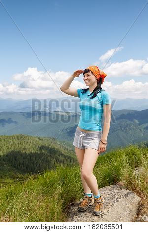 happy woman tourist admiring views of the mountains. Hiker girl relaxing on top of mountain and enjoying the view of valley. Healthy lifestyle, adventure, active leisure tourism and hiking concept