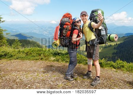 Couple of hikers taking selfie. Tourists woman and man in mountains make selfie uses mobile phone. Mountain selfie in summer. Healthy lifestyle, adventure, tourism, hiking and technology concept