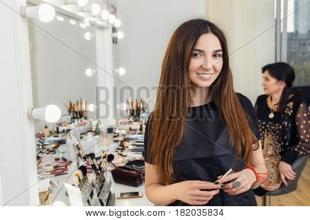 happy young makeup artist holding brush in hands. Visagiste ready to work on a client. Portrait of make-up artist in beauty salon. Real people