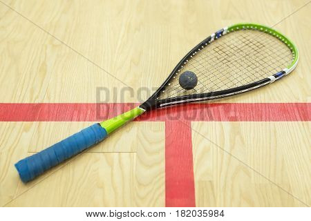 squash racket and ball on the wooden background. Racquetball equipment on the court near red line. Photo with selective focus