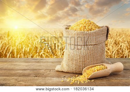 uncooked bulgur or couscous grains in sack on table with ripe field on the background. Agriculture and harvest concept. Golden wheat field on sunset. Healthy eating for diet and vegan