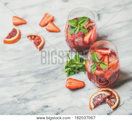 Blood orange and strawberry summer Sangria. Fruit refreshing rose wine cocktails in glasses with ice and fresh mint leaves over marble table background, selective focus, copy space